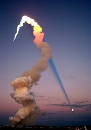 Shuttle Launch at Sunset. The sun is behind the camera, and the shadow of the plume is cast across the roof of the sky, intersecting the moon.